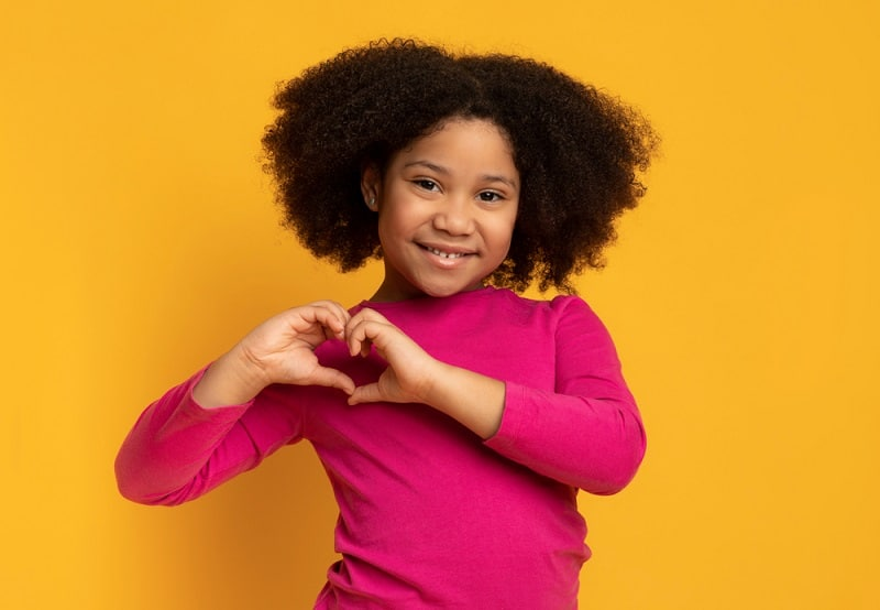 little girl making a heart shape with her hands