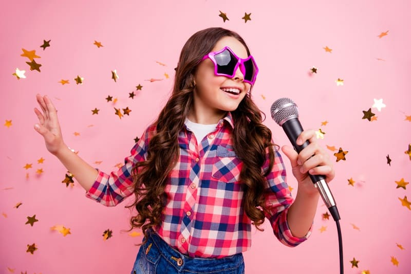 little girl with funny sunglasses singing and dancing in front of a pink background