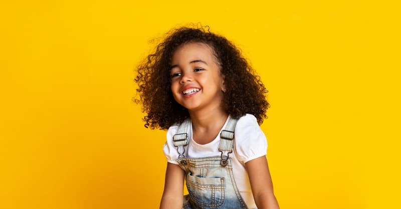 little girl with curly brown hair smiling in front of a yellow background