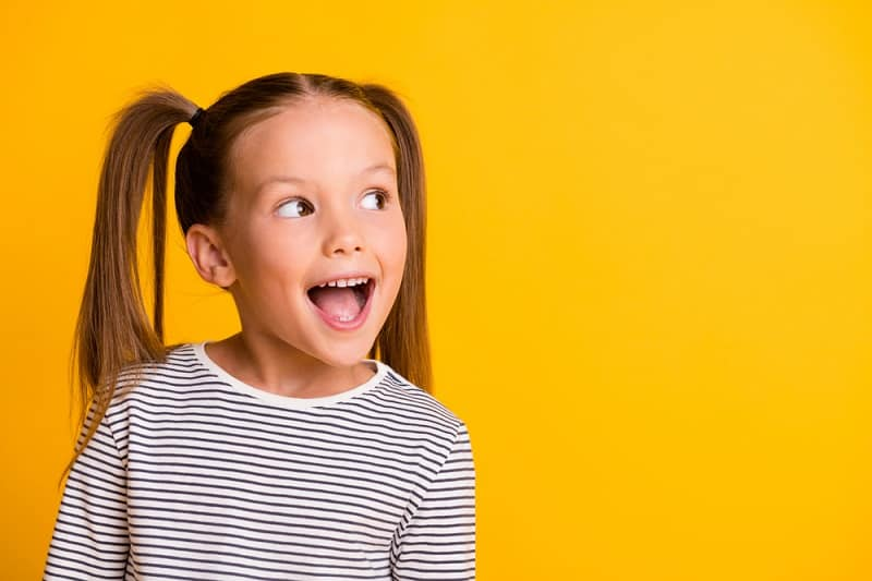 little girl with pigtails smiles and looks to the side