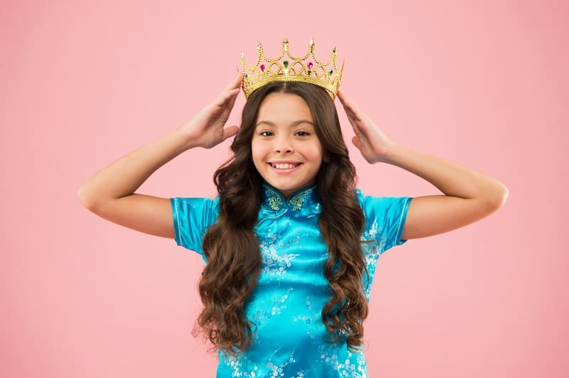little girl in a blue dress putting a golden crown on her head