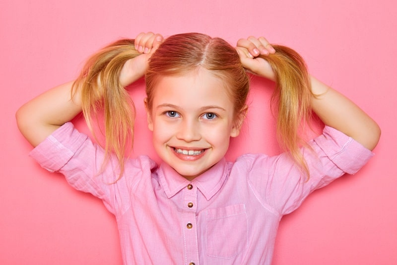 little girl with pigtails smiling in front of a pink background