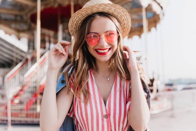 smiling woman wearing pink sunglasses