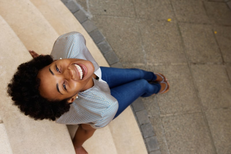 smiling young african woman sitting on steps