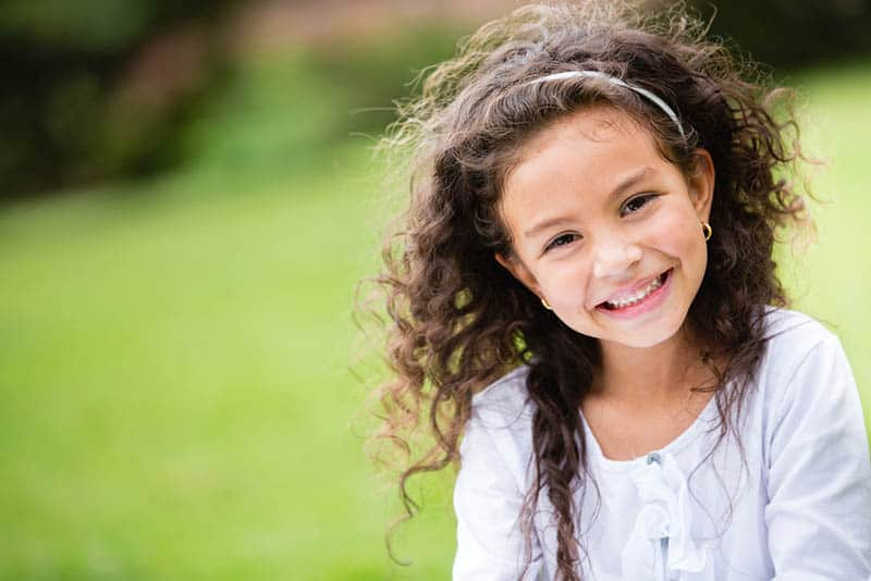 sweet little girl with curly hair smiling and posing outdoor