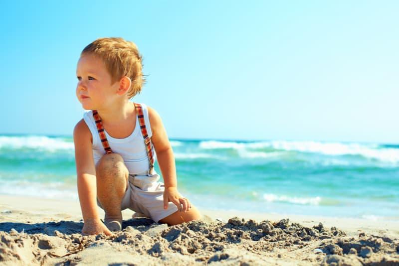 thoughtful boy sitting on the beach