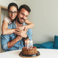 a woman hugs her husband on his birthday and gives him a birthday cake