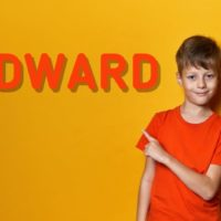 cute young boy with orange t-shirt pointing to the name Edward