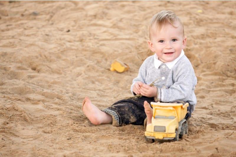 Boy sitting on sandpit and smiling
