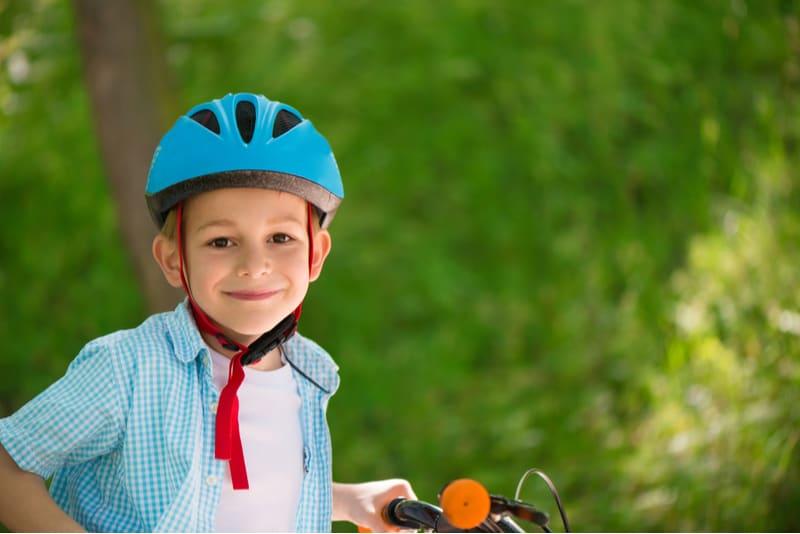Cute little boy wearing helmet in forest