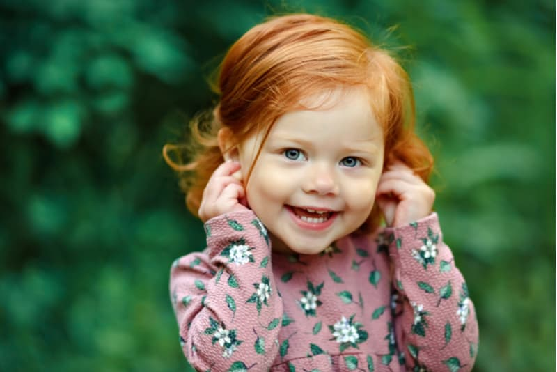 Little beautiful red-haired little girl smiling