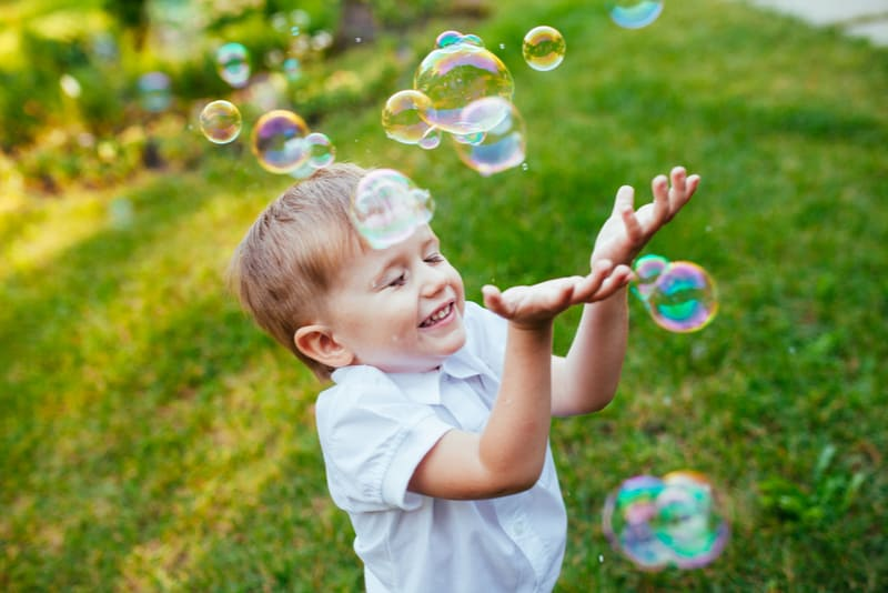 Little boy playing with soap bubbles in the park