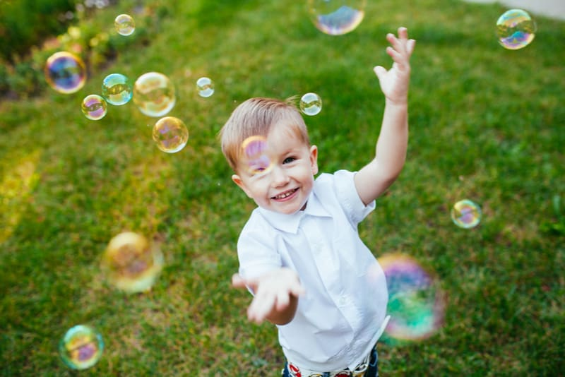 Little boy with soap bubbles in summer park
