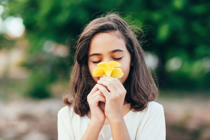 Little girl smelling a flower in the garden