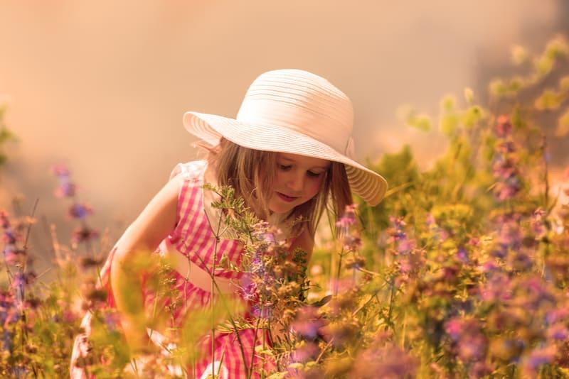 Little girl smelling flowers in the meadow