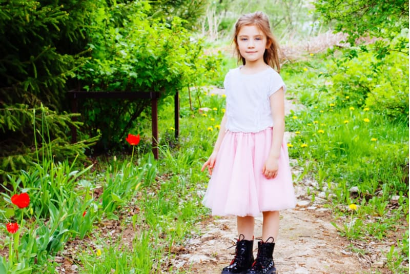 Little girl wearing pink skirt standing on the road