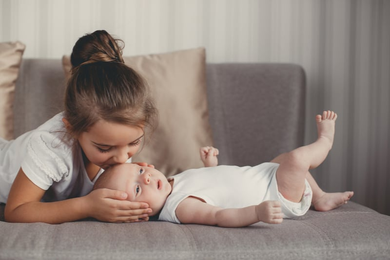 Little sister kissing her newborn brother