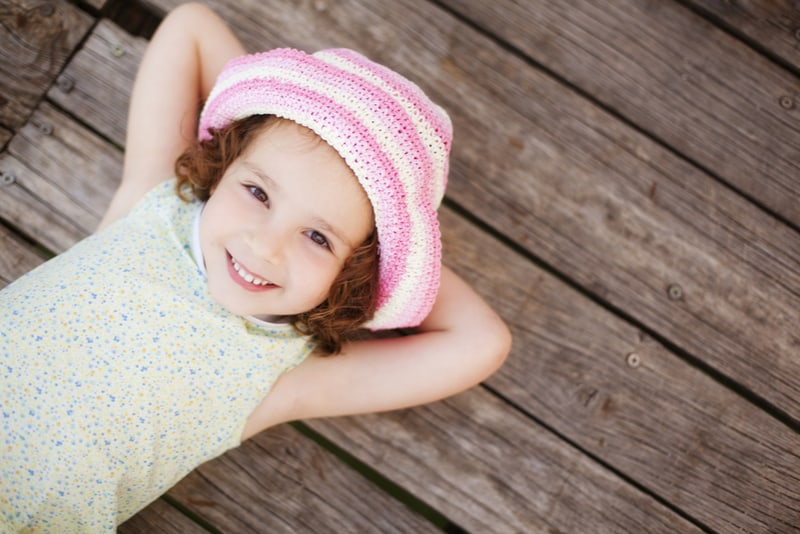 Pretty child lying on wooden surface