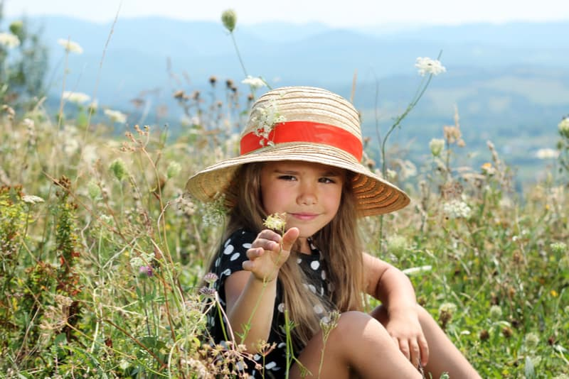 Pretty little girl wearing dress and straw hat