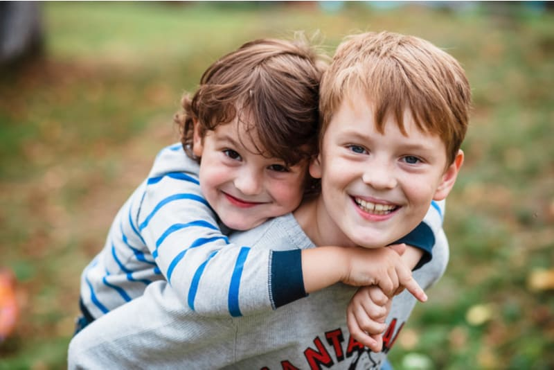 Two happy brothers hugging and smiling