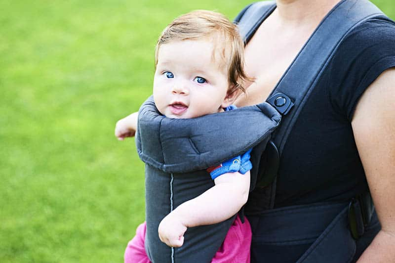 Young mother with her little baby child girl in a carrier outside in nature