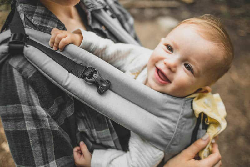 adorable baby smiling in the carrier on his mother