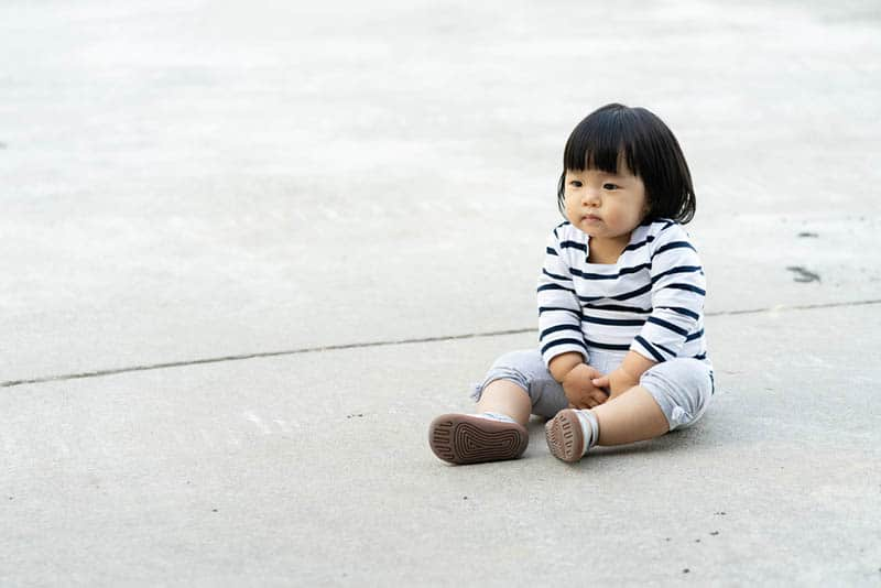 adorable little girl needs to pee while sitting outdoor