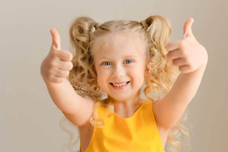 adorable little girl showing double thumbs-up