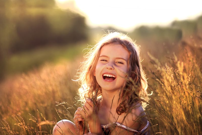 adorable little girl sitting in a meadow and smiling a lot