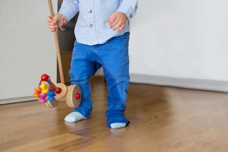 baby boy peeing in pants while holding a toy