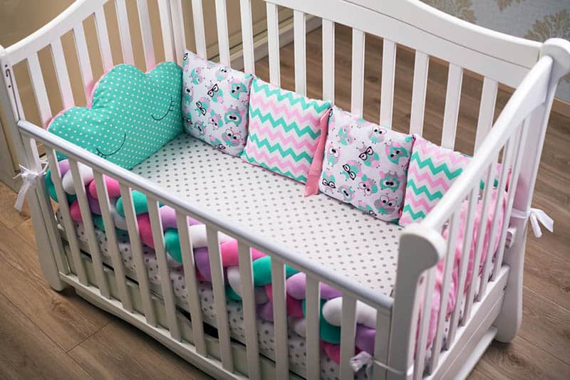 baby crib with colorful rail and pillows