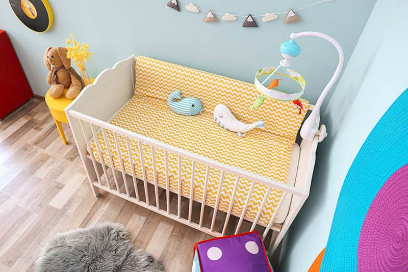 baby crib with toys and baby items in the bedroom