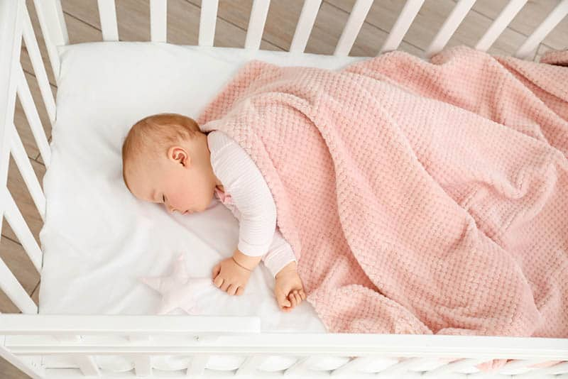 baby sleeping in crib covered with pink blanket
