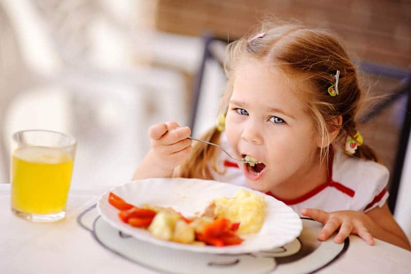 beautiful little girl eating a lunch