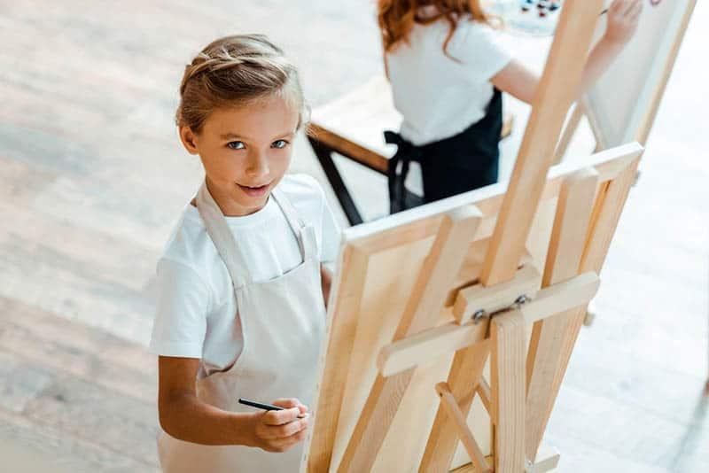 beautiful little girl looking at camera in art school