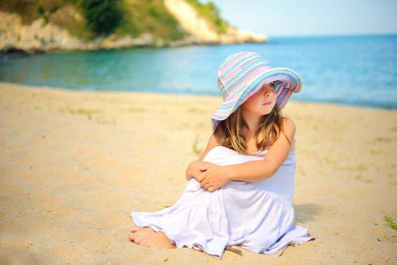 beautiful little girl sits on the beach