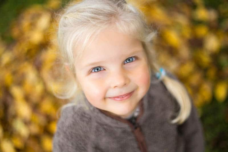 beautiful little girl with blond hair and blond eyes looking up