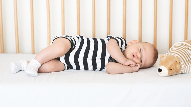 cute baby boy sleeping in a crib with toy next to him