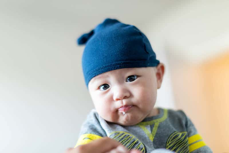 cute baby boy wearing blue hat and spitting up