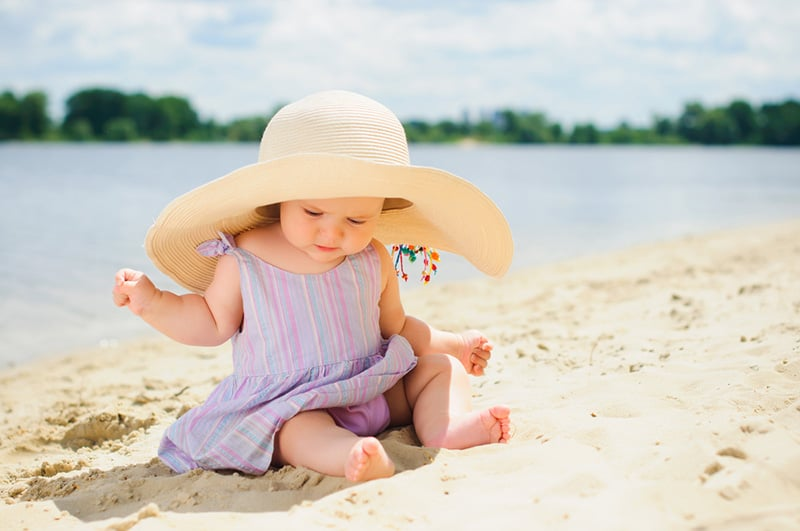cute baby girl wearing big hat and playing on the beach sand