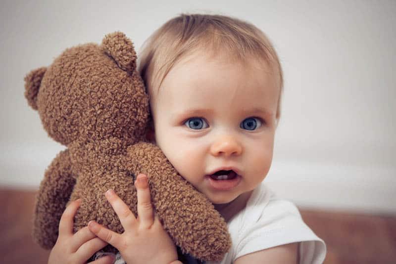 cute baby girl with blue eyes cuddling with teddy bear