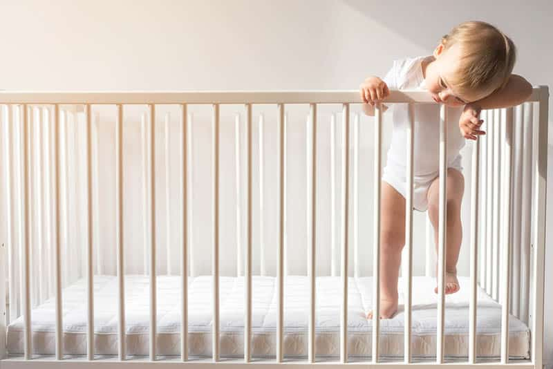 cute baby wearing white onesie standing in the crib and biting a rail