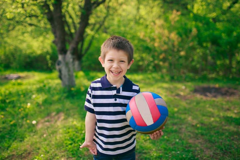 cute little boy holding ball