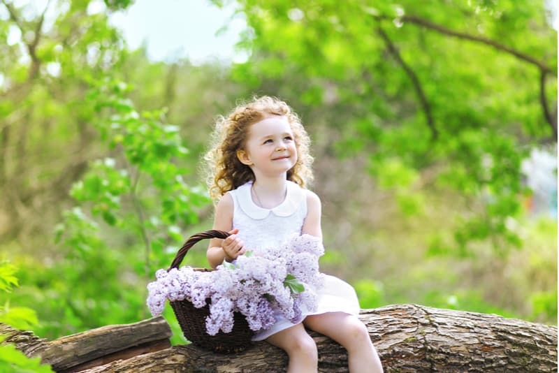 cute little curly girl sitting in the forest