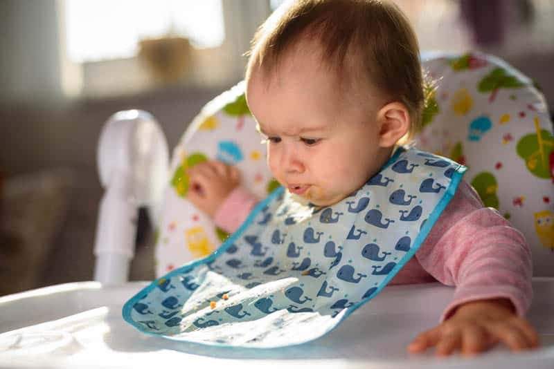 funny baby girl eating in a high chair