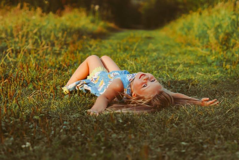cute little girl lying on the green grass