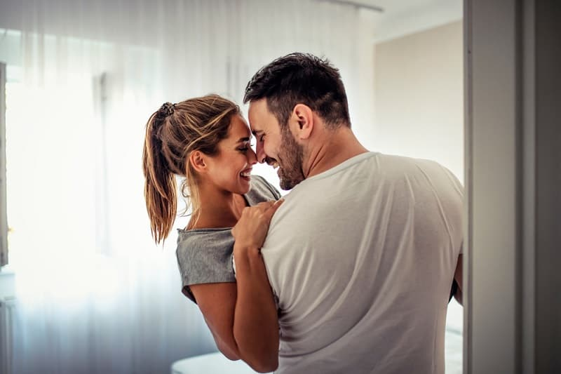 happy couple embracing at home in their bedroom