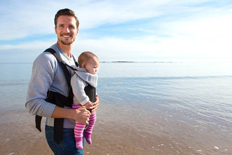 happy father carrying baby in the carrier on the beach