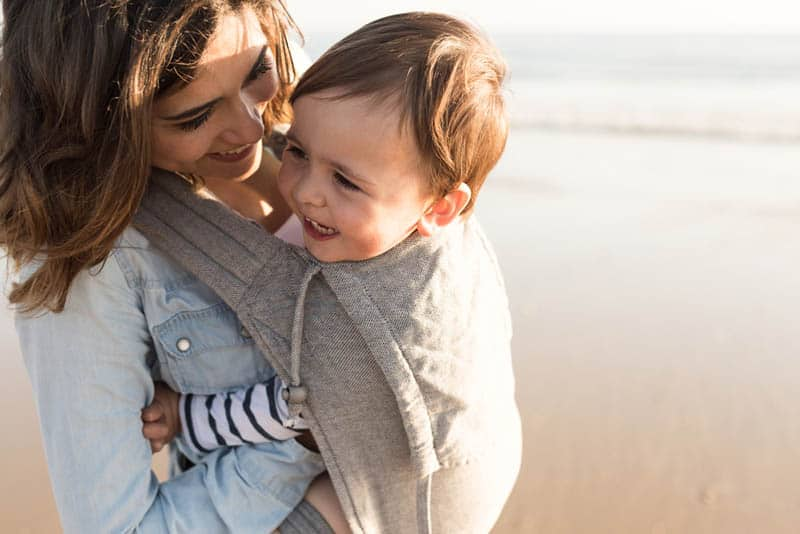 happy mother smiling with baby in a carrier on the beach