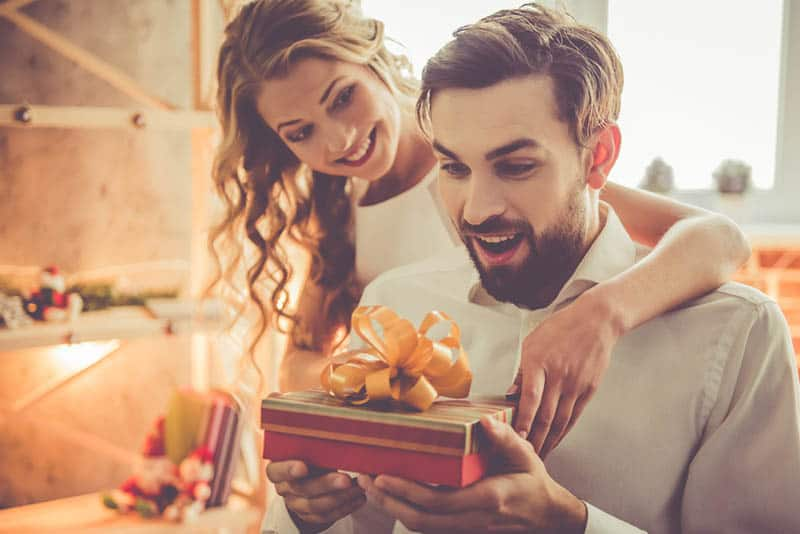 happy woman surprising her husband with birthday gift